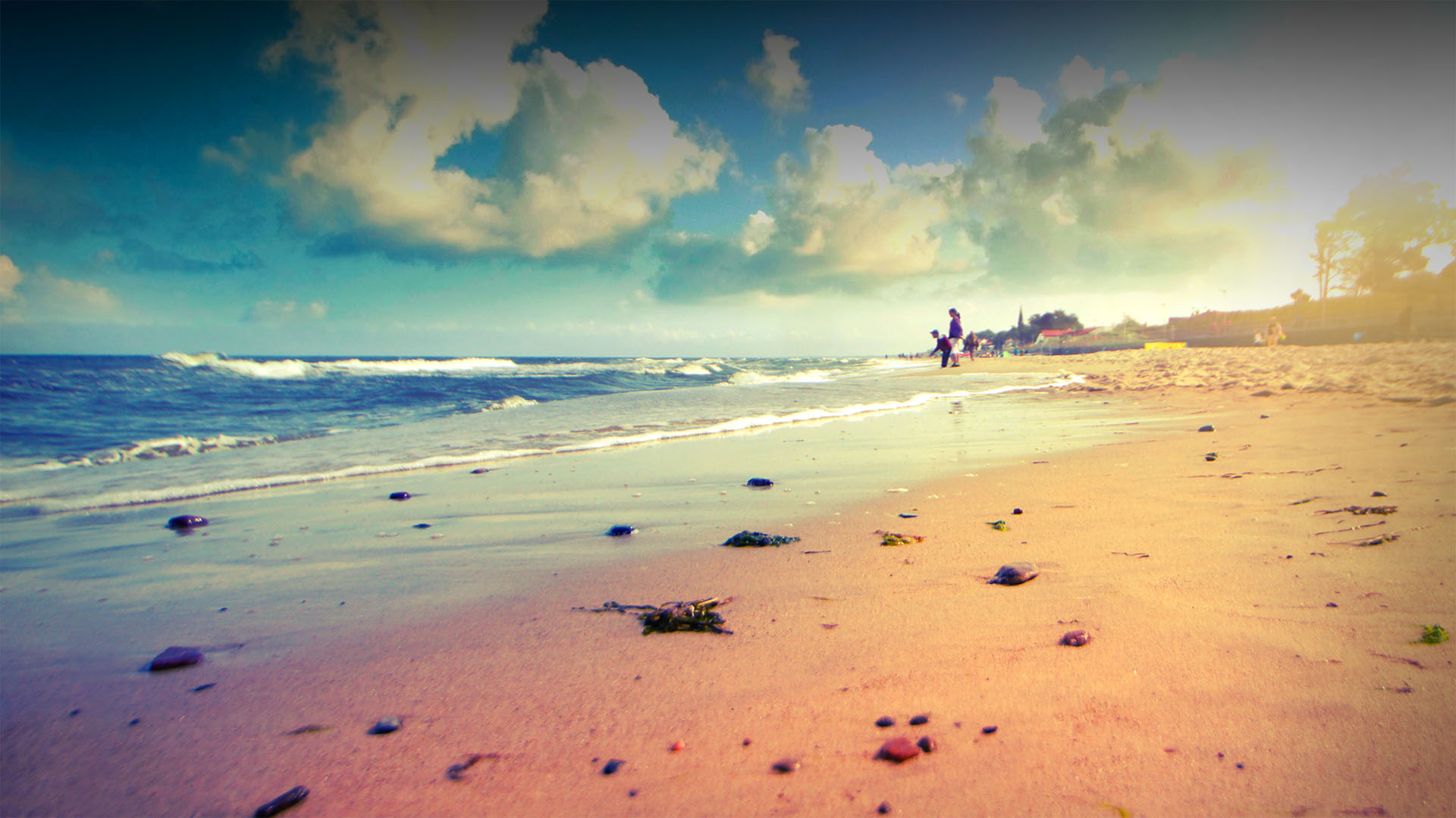 Nieduże fale, piasek, na niebie piękne chmury.